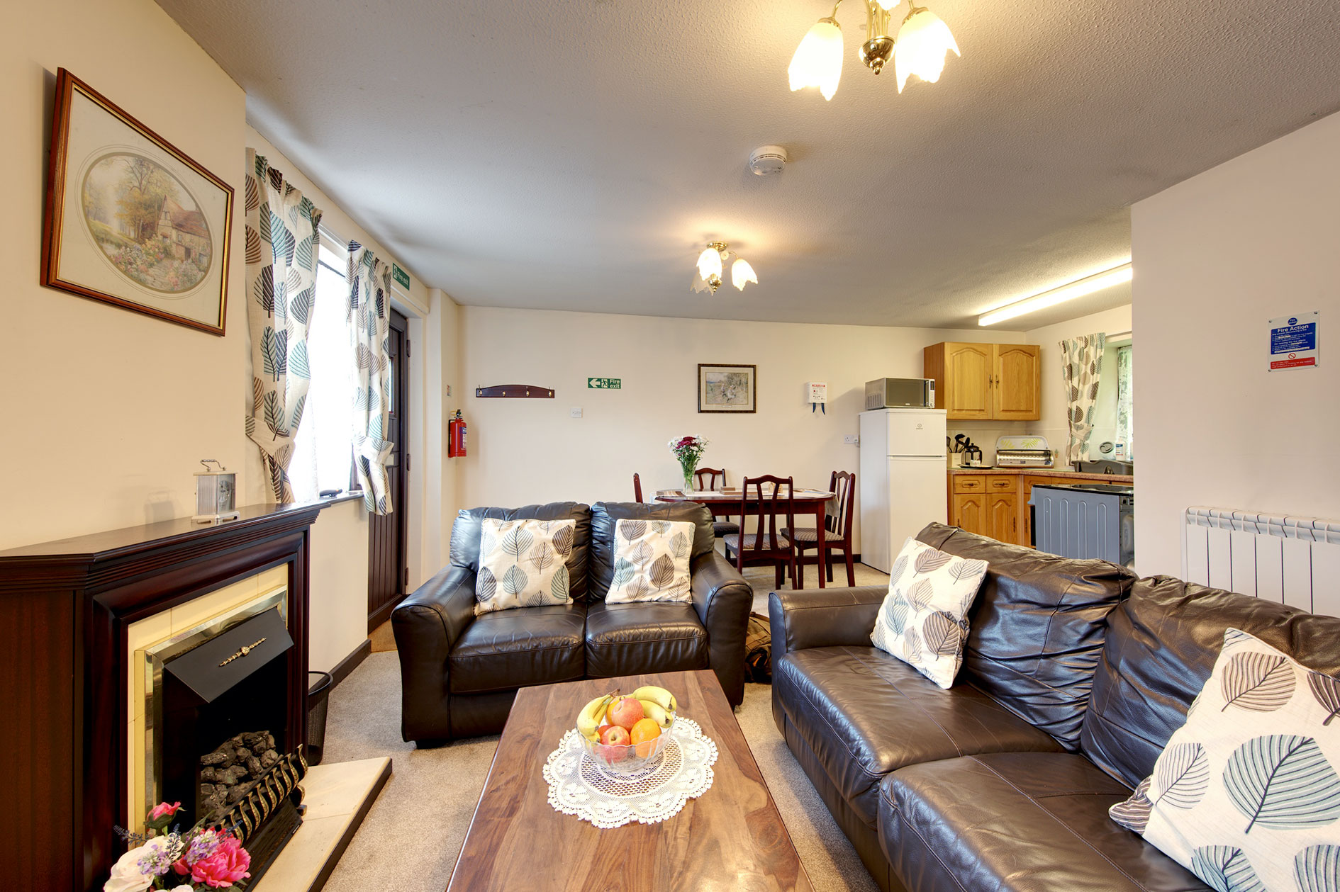 Living Room With Brown Leather Sofas And Kitchen And Dining Areas