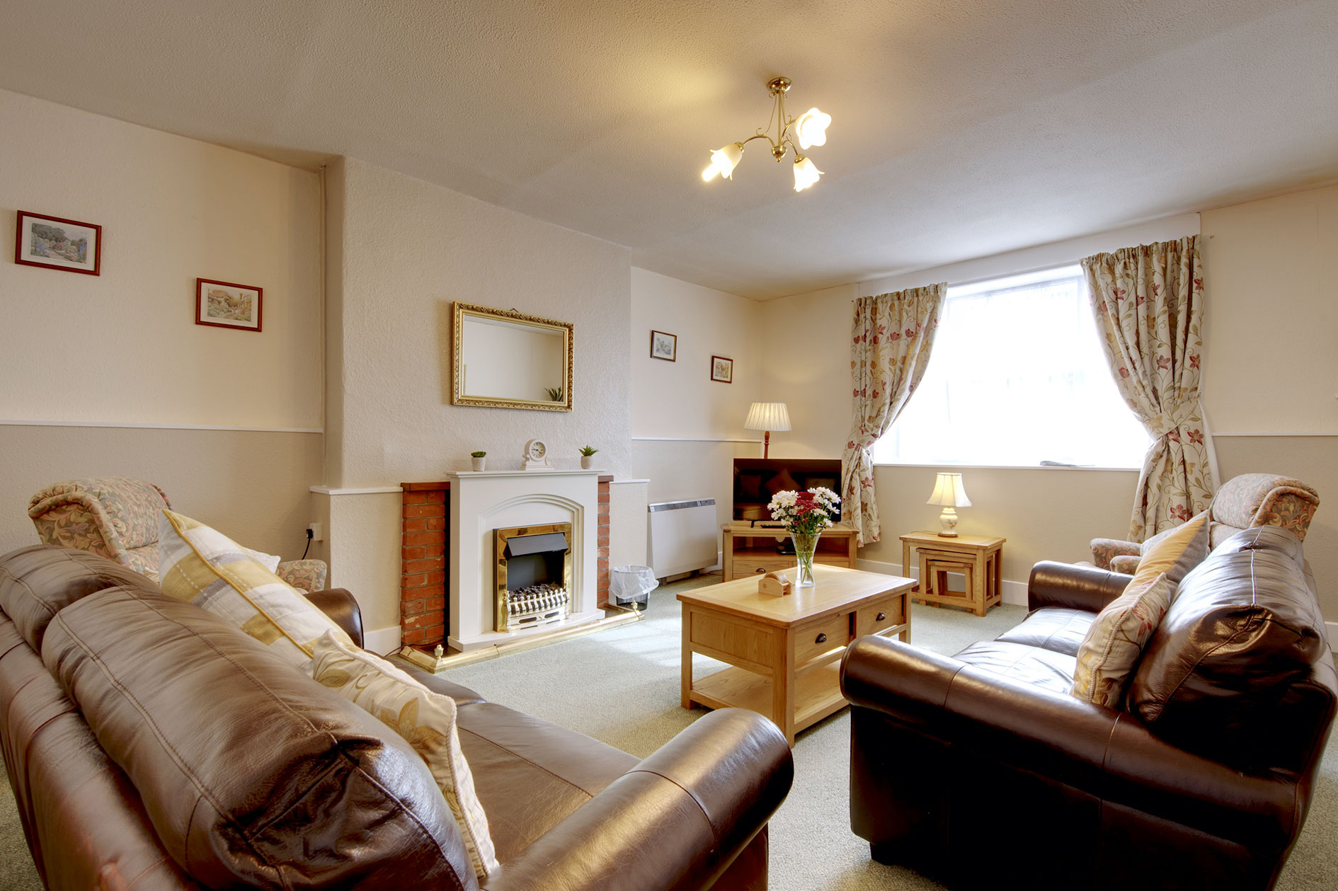 Living Room With Brown Leather Sofas, Tv, Feature Fireplace And Floral Curtains