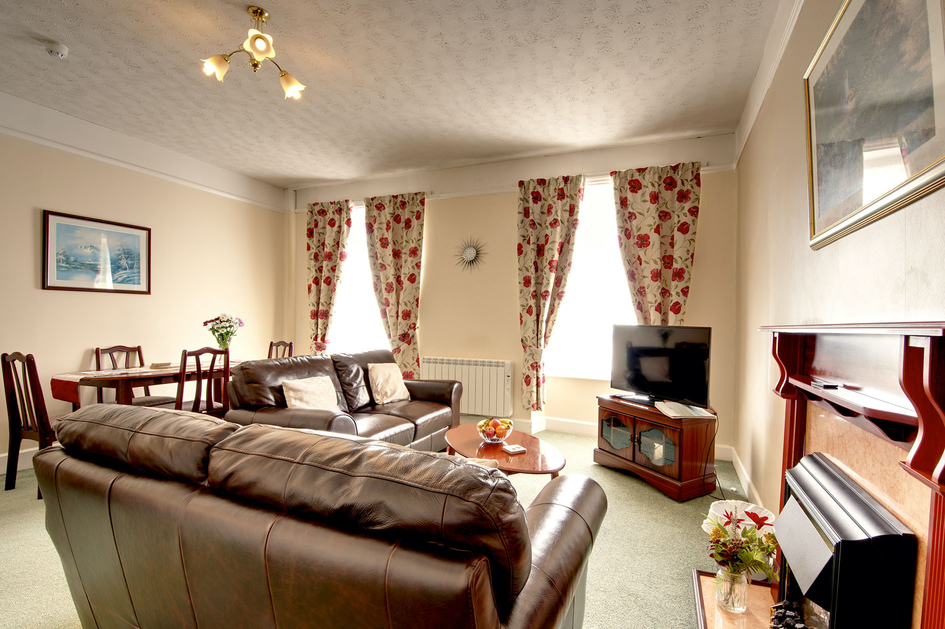 Living Room With Brown Leather Sofas, Tv And Red Floral Curtains