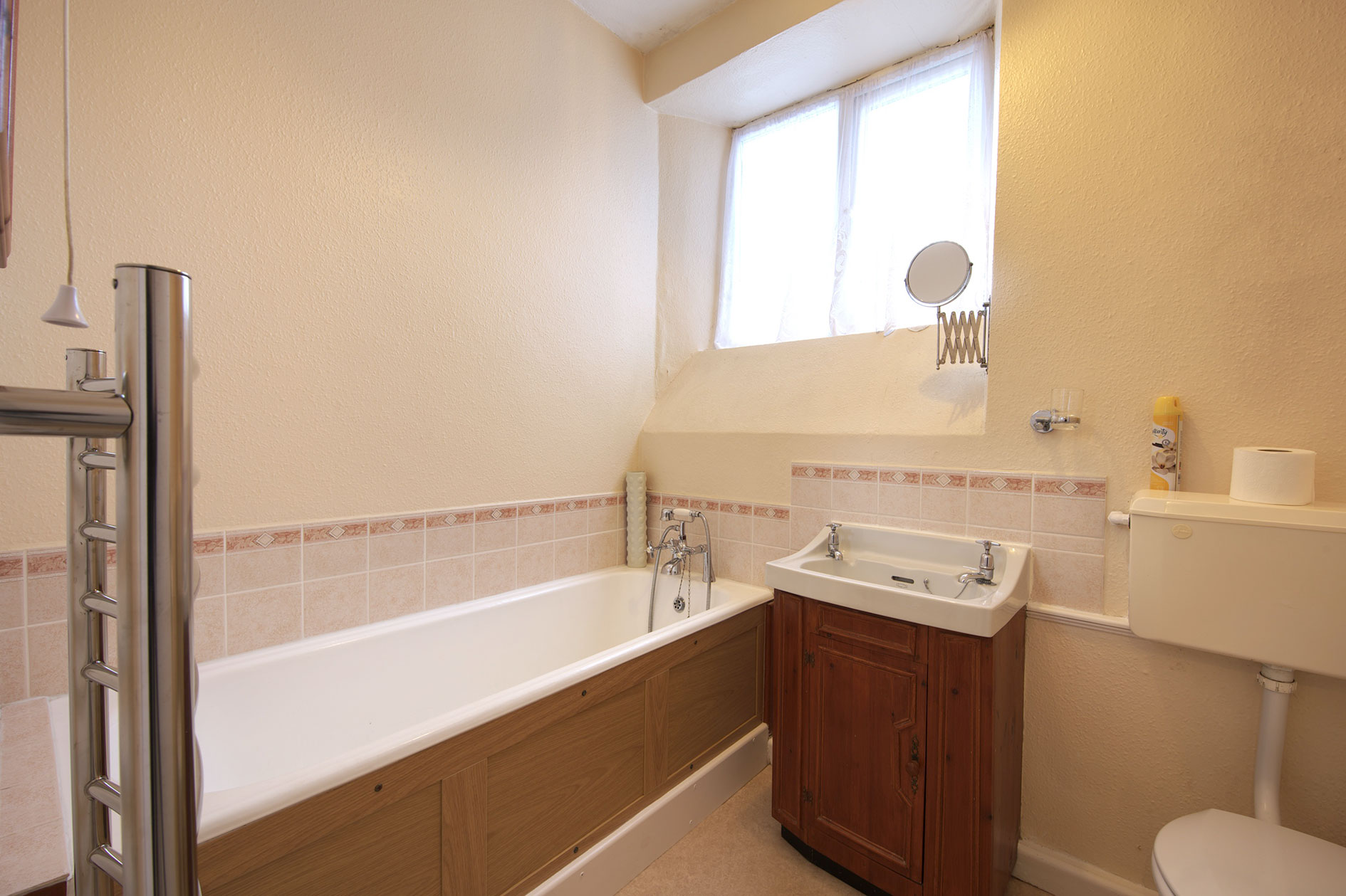 Light Bathroom With Wood Panelled Bath, Sink And Toilet