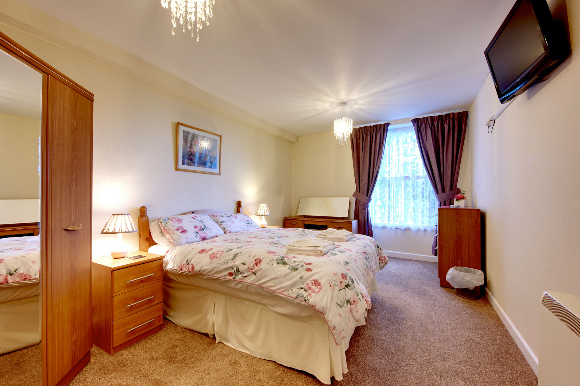 Lit Bedroom Containing A Double Bed With Red Flower Covers Plus Wooden Furniture And Tv