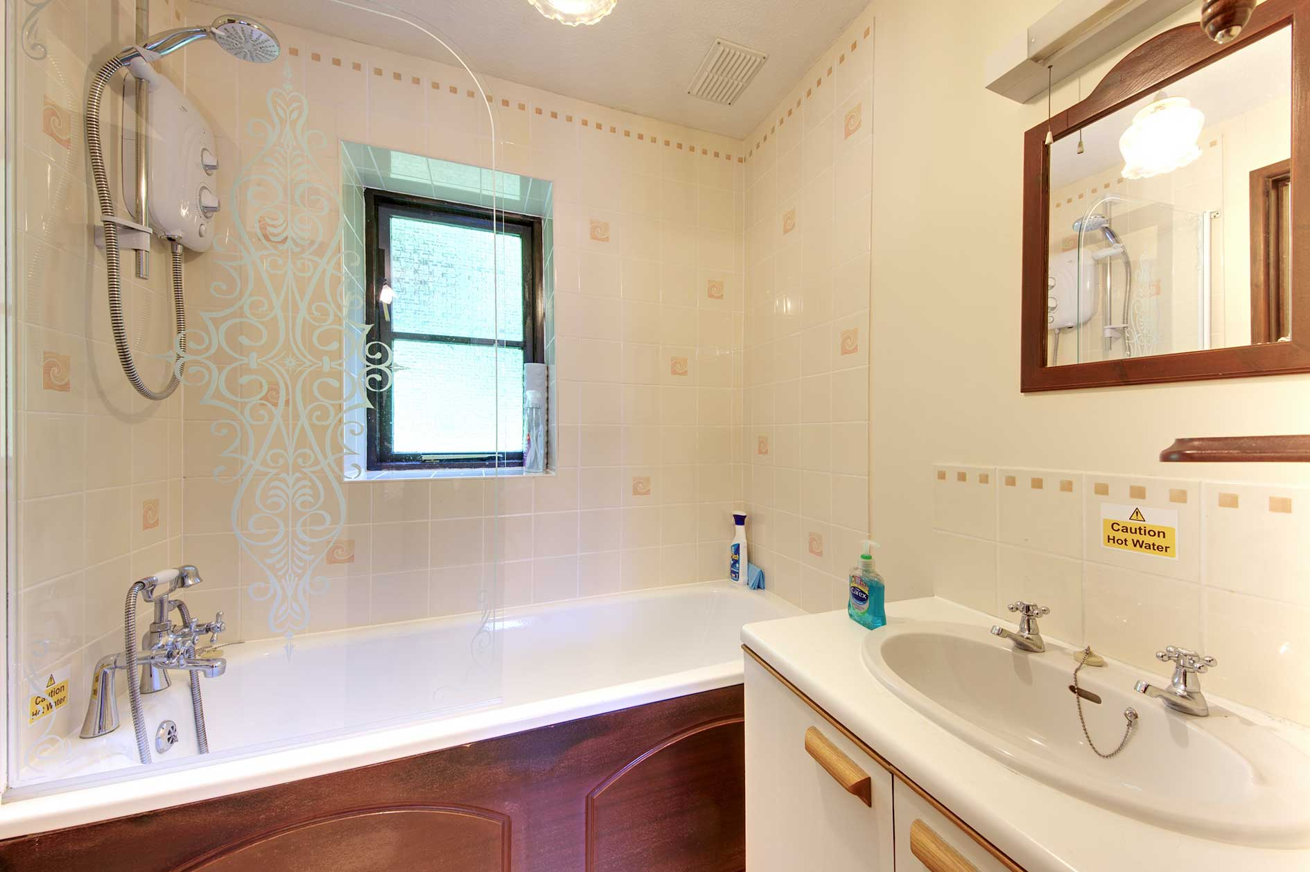 Light Bathroom With Wood Panelled Bath With Shower Over, Mirror And Sink