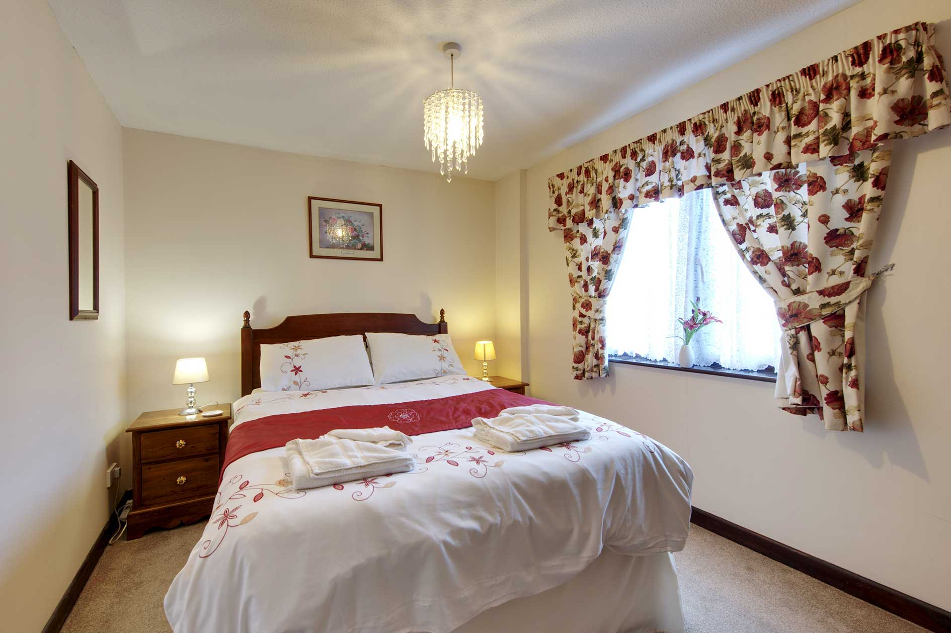 Bedroom Containing A Double Bed With Red Flower Covers And Curtains Plus Wooden Bedside Table