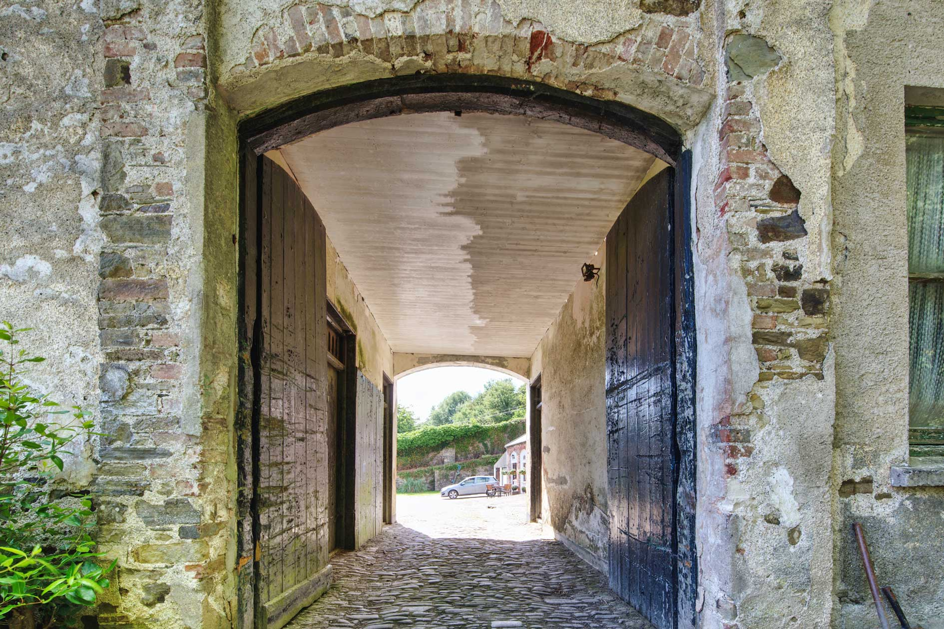 View Through Old Stone Arch With Dark Wooden Doors And Cobbled Floor