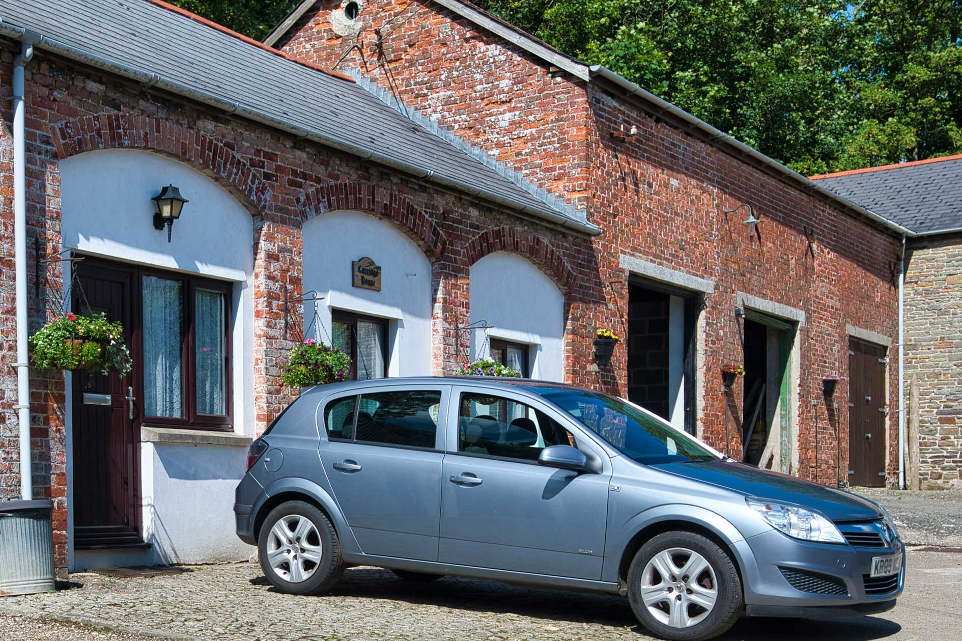 Silver Car Parked Outside Red Brick Converted Stable Building
