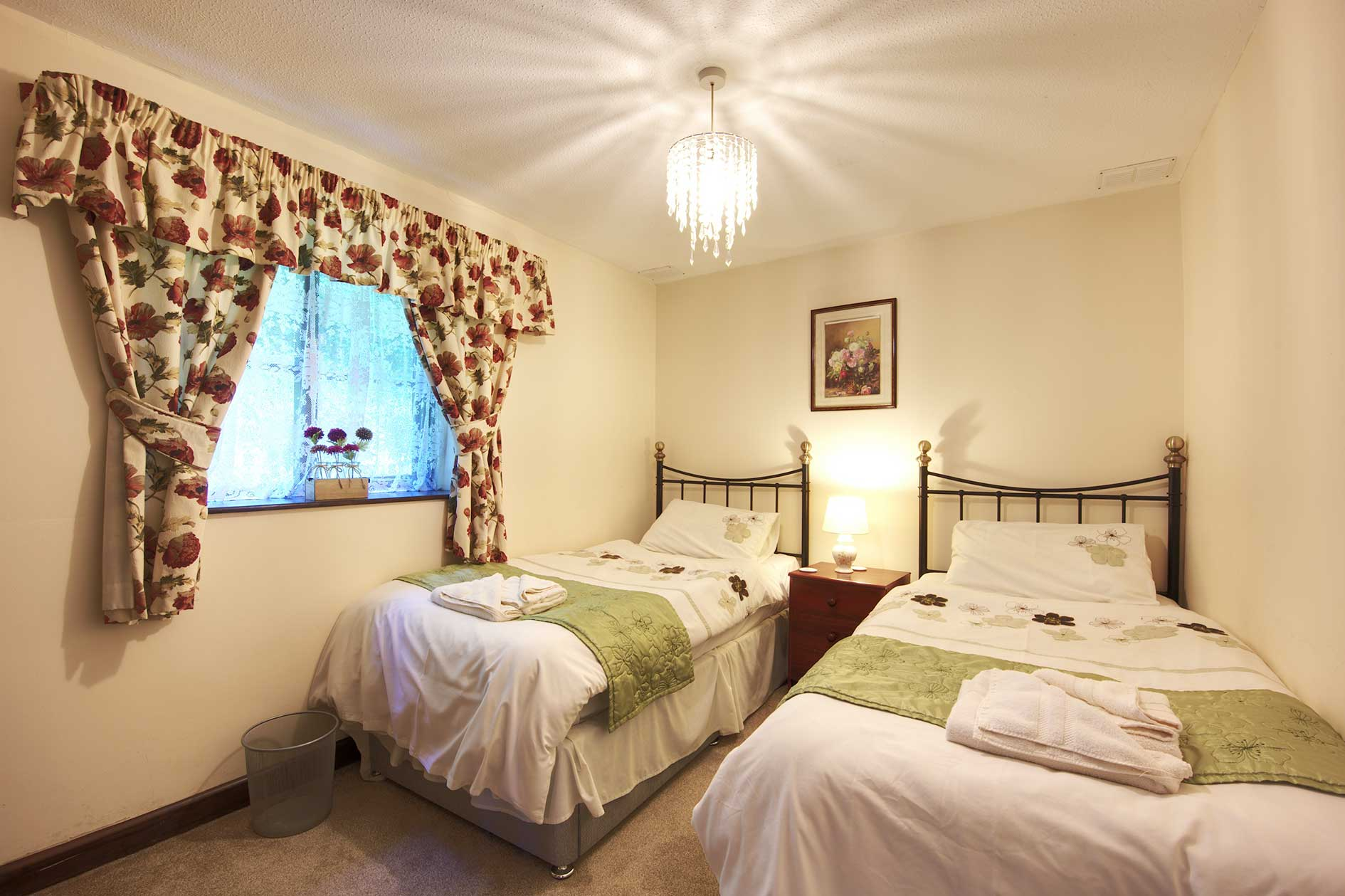 Light Bedroom With Two Single Beds With Black Metal Bedstead, White Linen And Red Floral Curtains