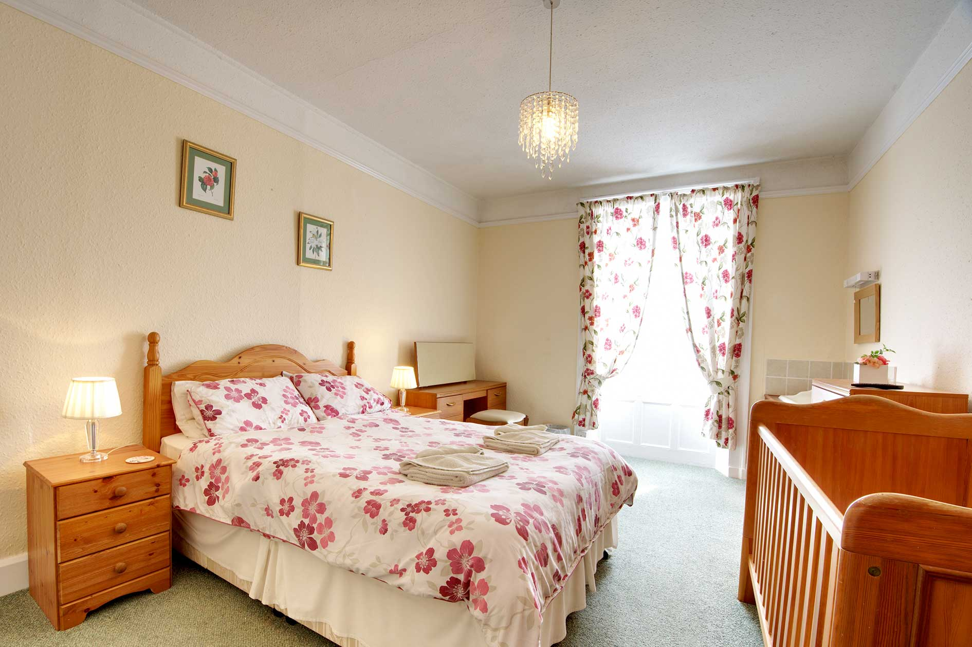 Light Bedroom With Double Bed With Red Flower Covers And Wooden Furniture Including A Cot