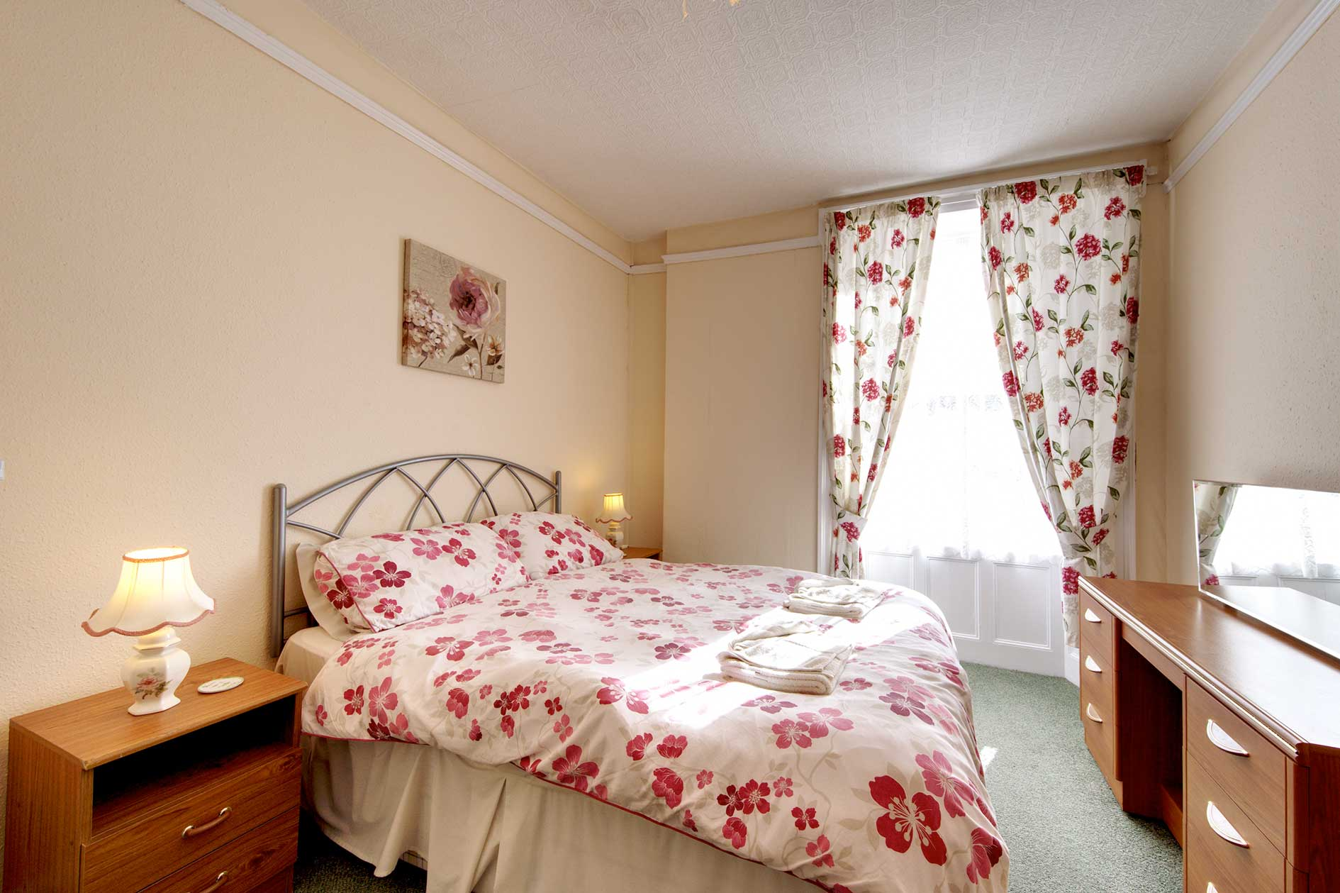 Light Bedroom With Double Bed With Red Flower Covers And Wooden Furniture
