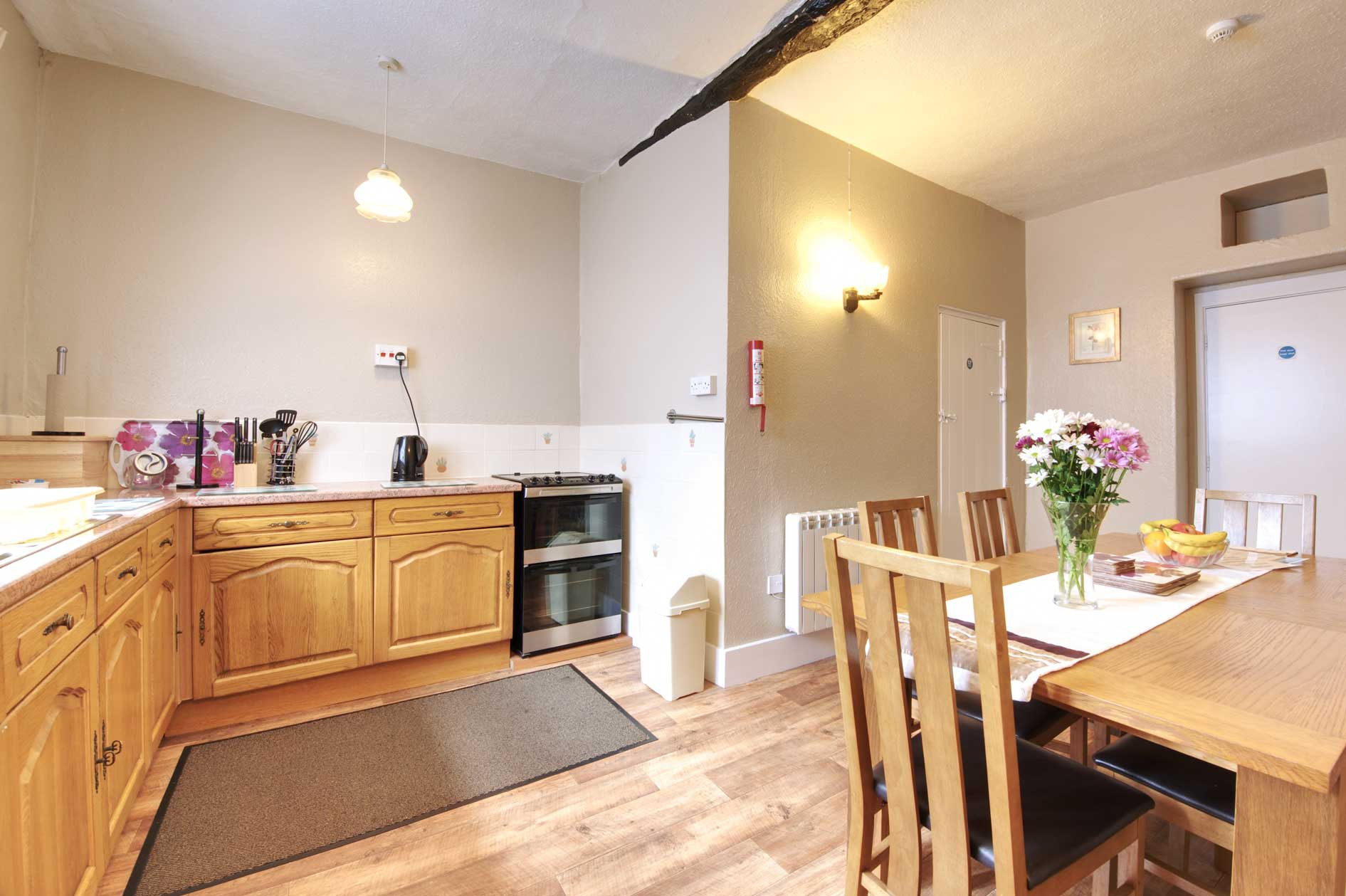 Light Kitchen With Wooden Cupboards And Kitchen Table