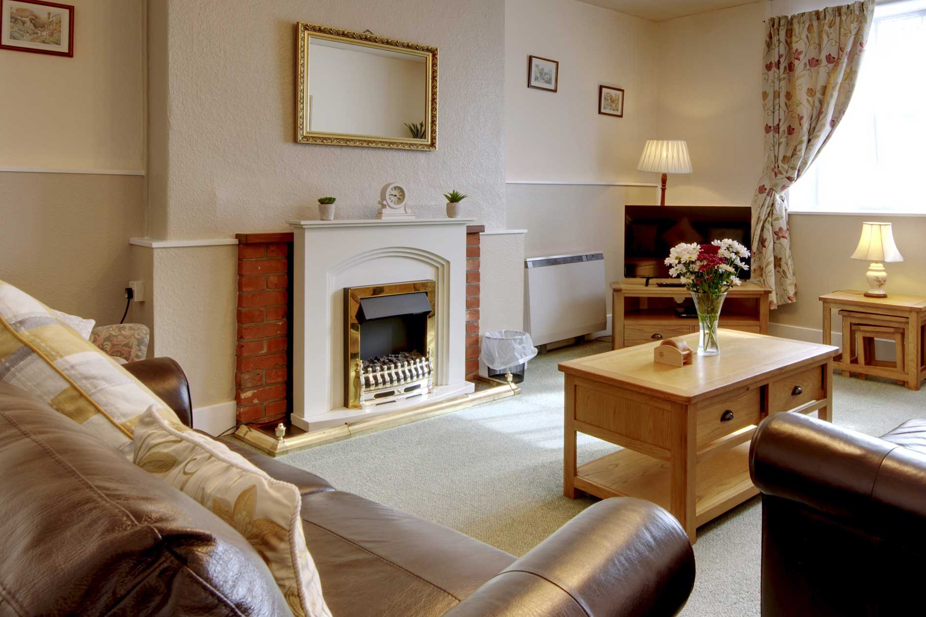 Living Room With Brown Leather Sofas, Wooden Furniture And Fire Mantle