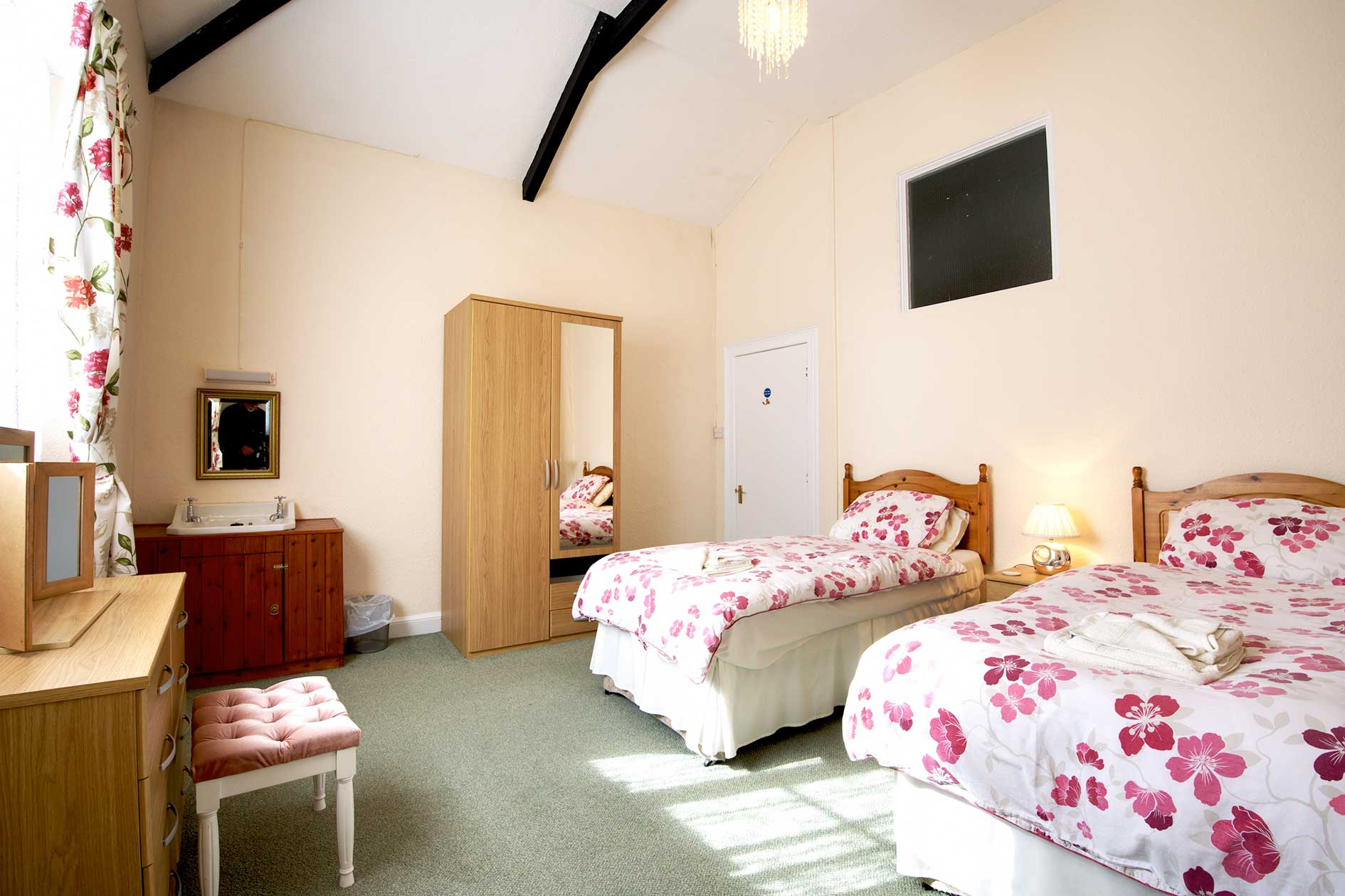 Light Bedroom With Two Single Beds With Red Flower Covers And Wooden Furniture