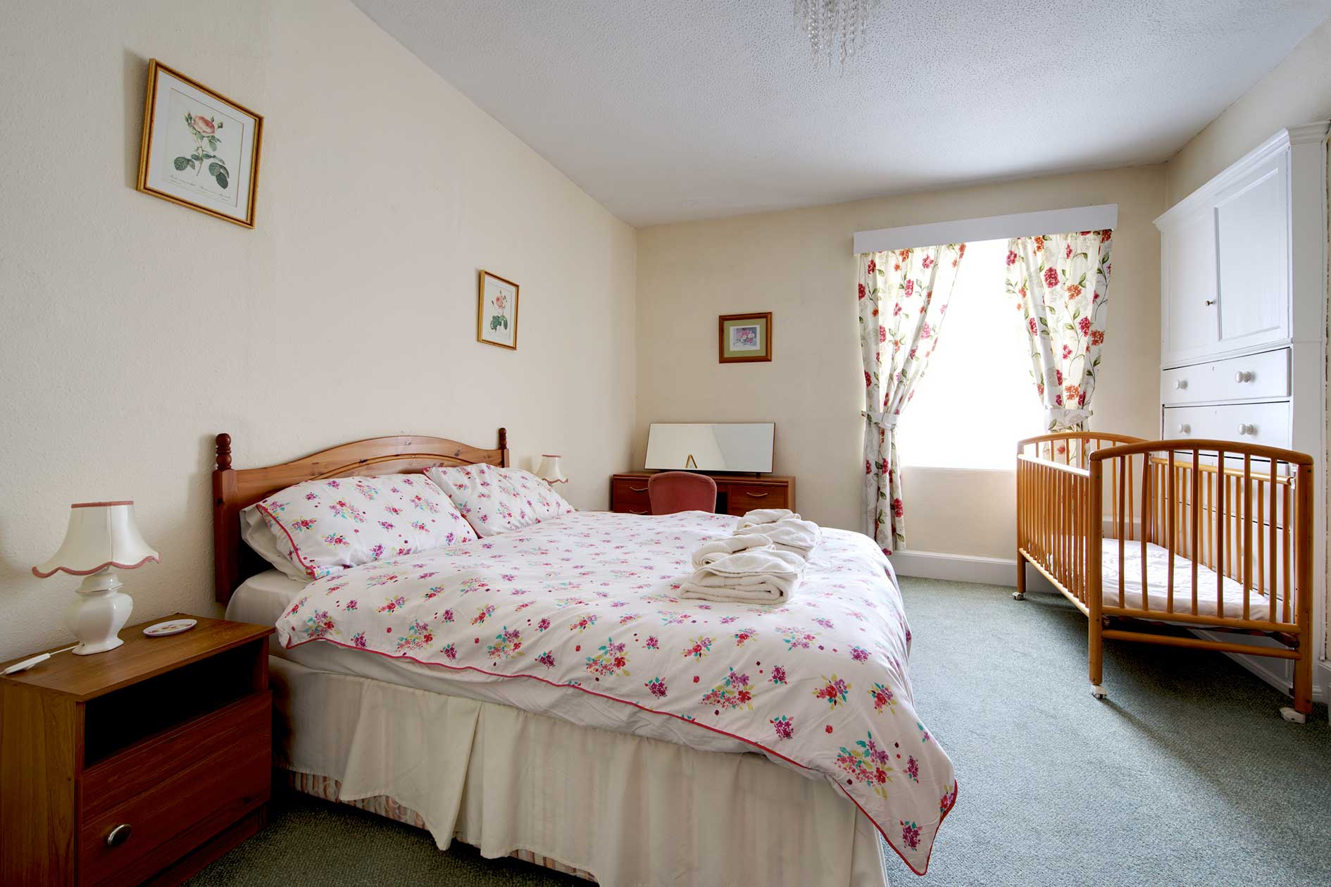 Light Bedroom Containing A Double Bed With Red Flower Covers And Curtains Plus Wooden Furniture Including A Cot