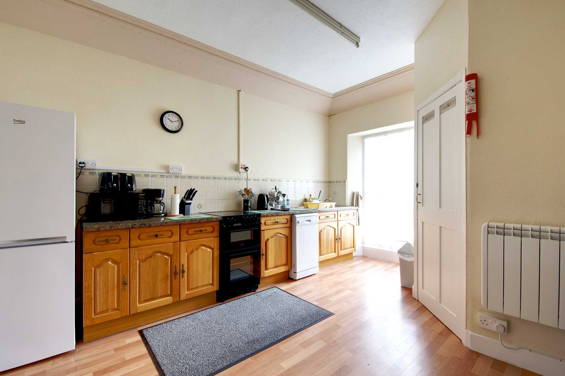 Light Kitchen With Wooden Cupboards And Granite Effect Worktop