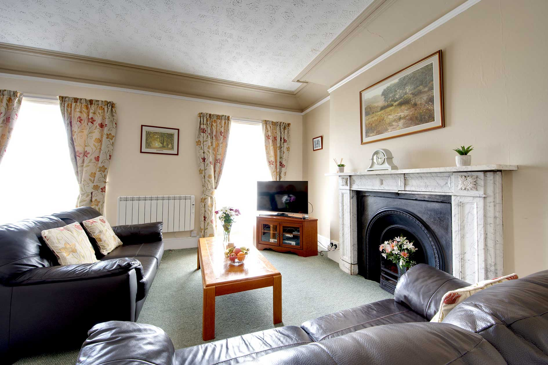 Living Room With Brown Leather Sofas, Feature Fireplace And Red Floral Curtains