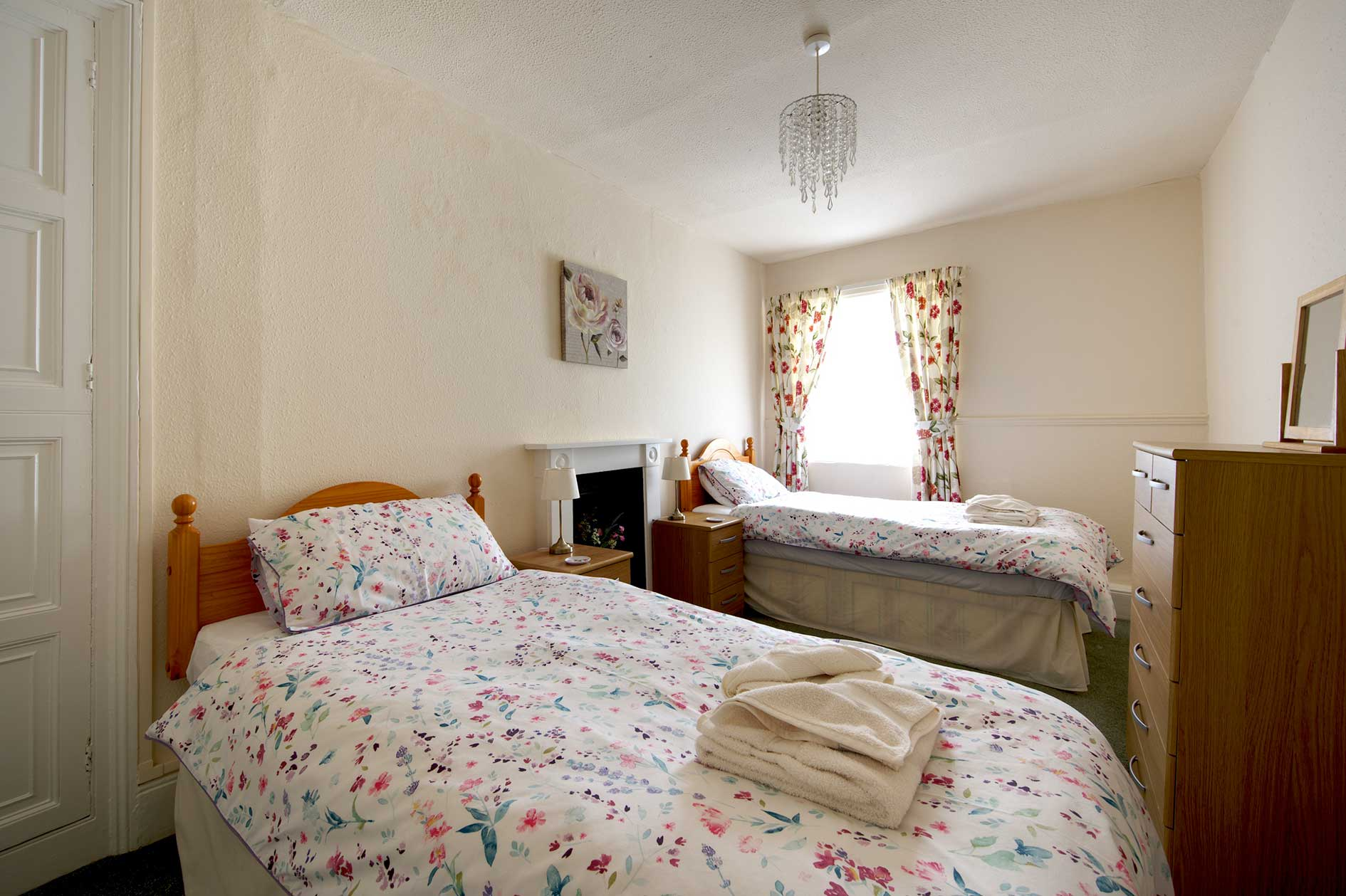 Light Bedroom With Two Single Beds With Floral Covers And Wooden Furniture