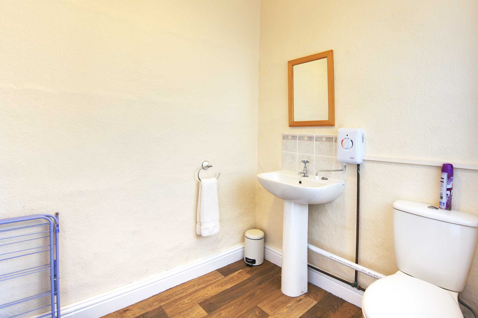 Light Bathroom With White Sink And Toilet And Wooden Floor