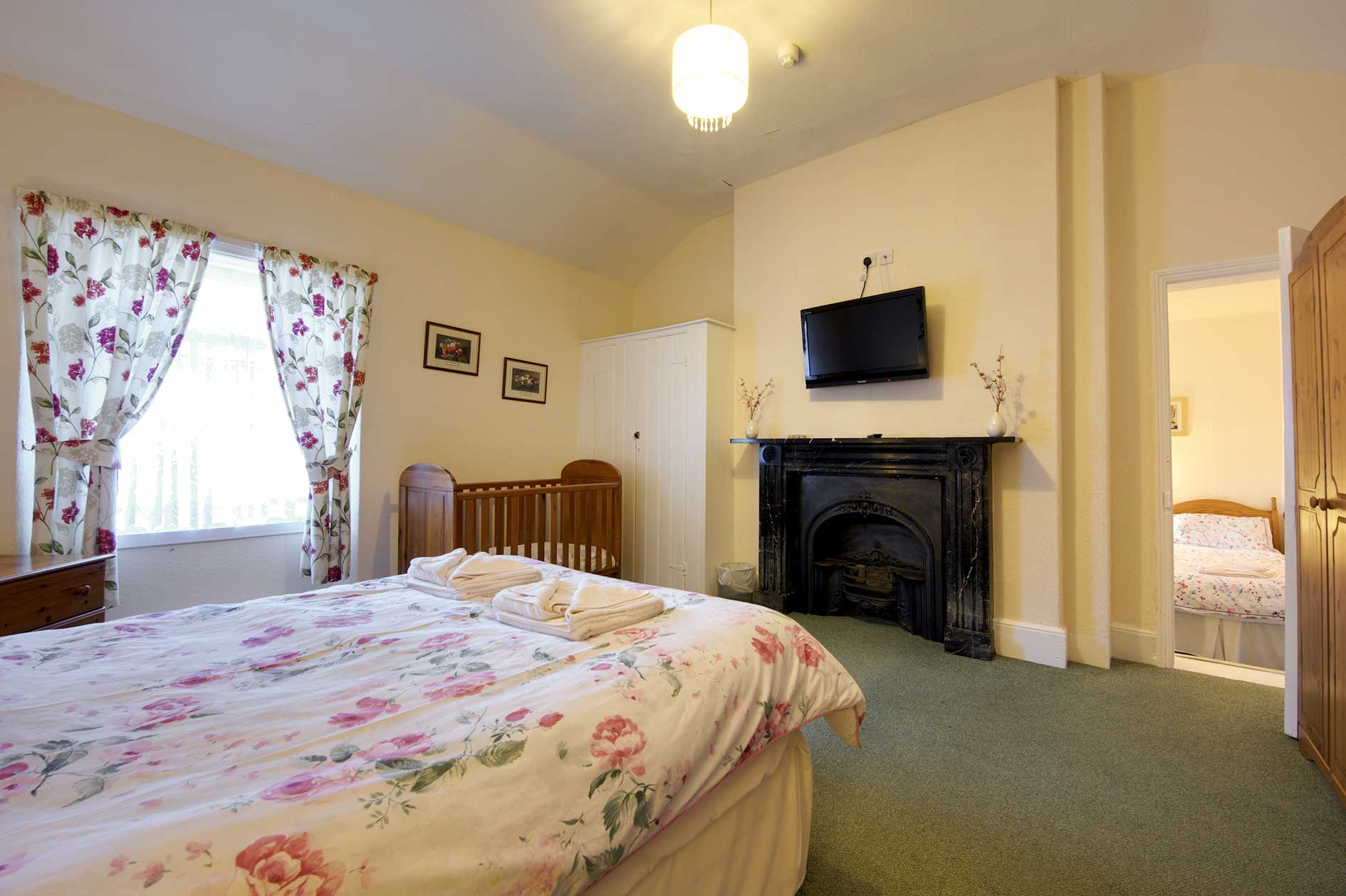 Light Bedroom Containing A Double Bed With Red Flower Covers And Curtains Plus Wooden Furniture And Black Victorian Fireplace