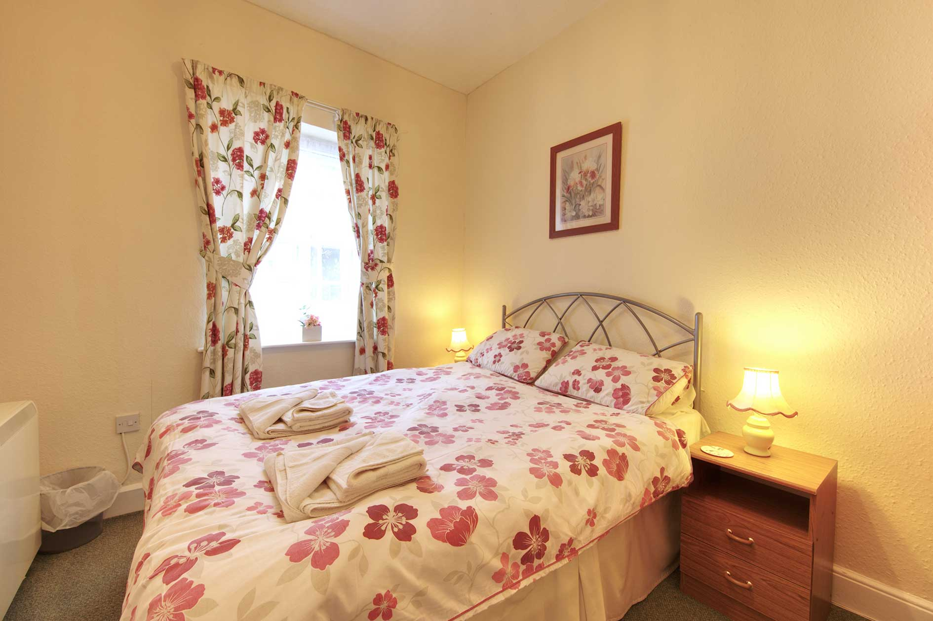 Lit Bedroom Containing A Double Bed With Red Flower Covers And Curtains Plus Wooden Furniture