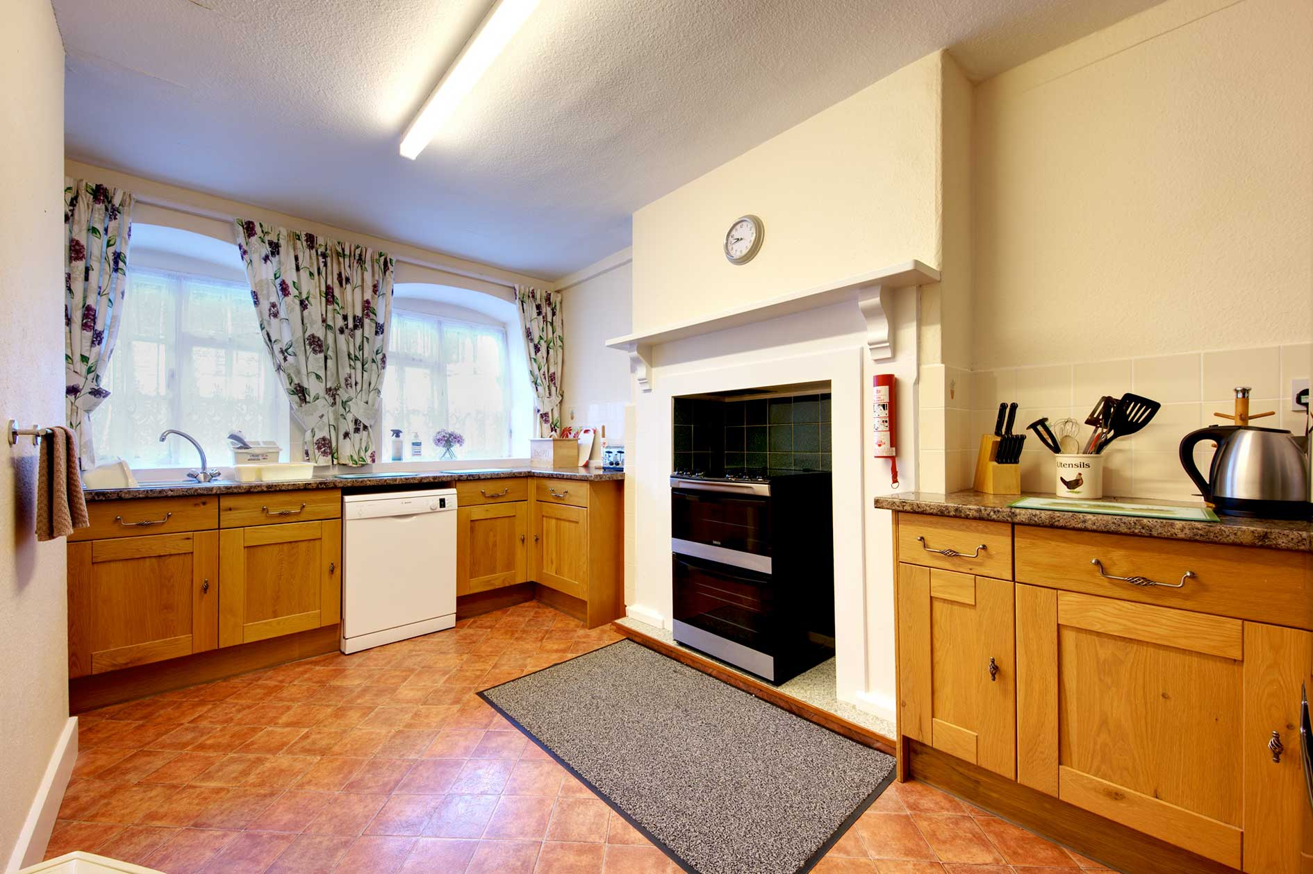 Light Kitchen With Wooden Cupboards, Black Cooker And Granite Effect Worktop