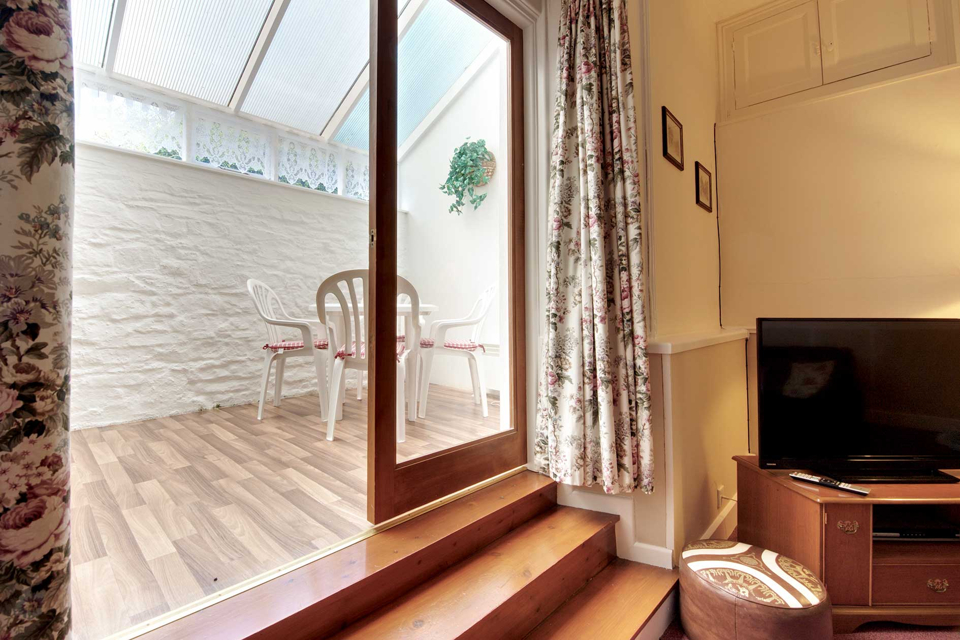 Glass Doors Leading To Small Conservatory With White Chairs And Table