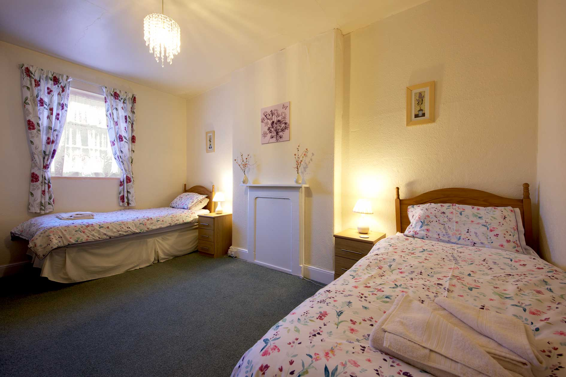 Lit Bedroom With Two Single Beds With Floral Covers And Wooden Furniture