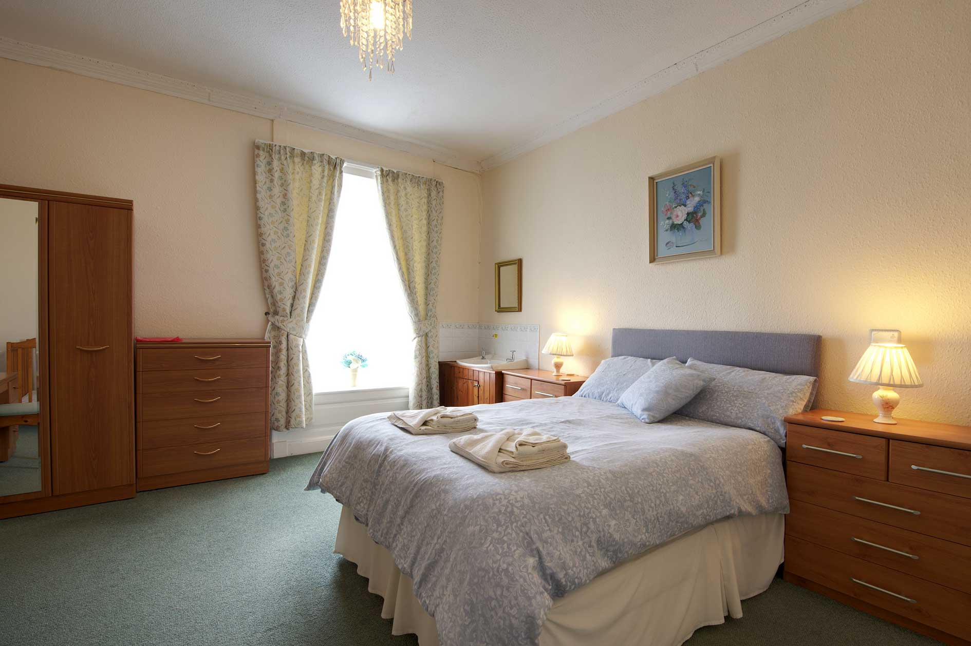 Light Bedroom With Double Bed And Wooden Furniture