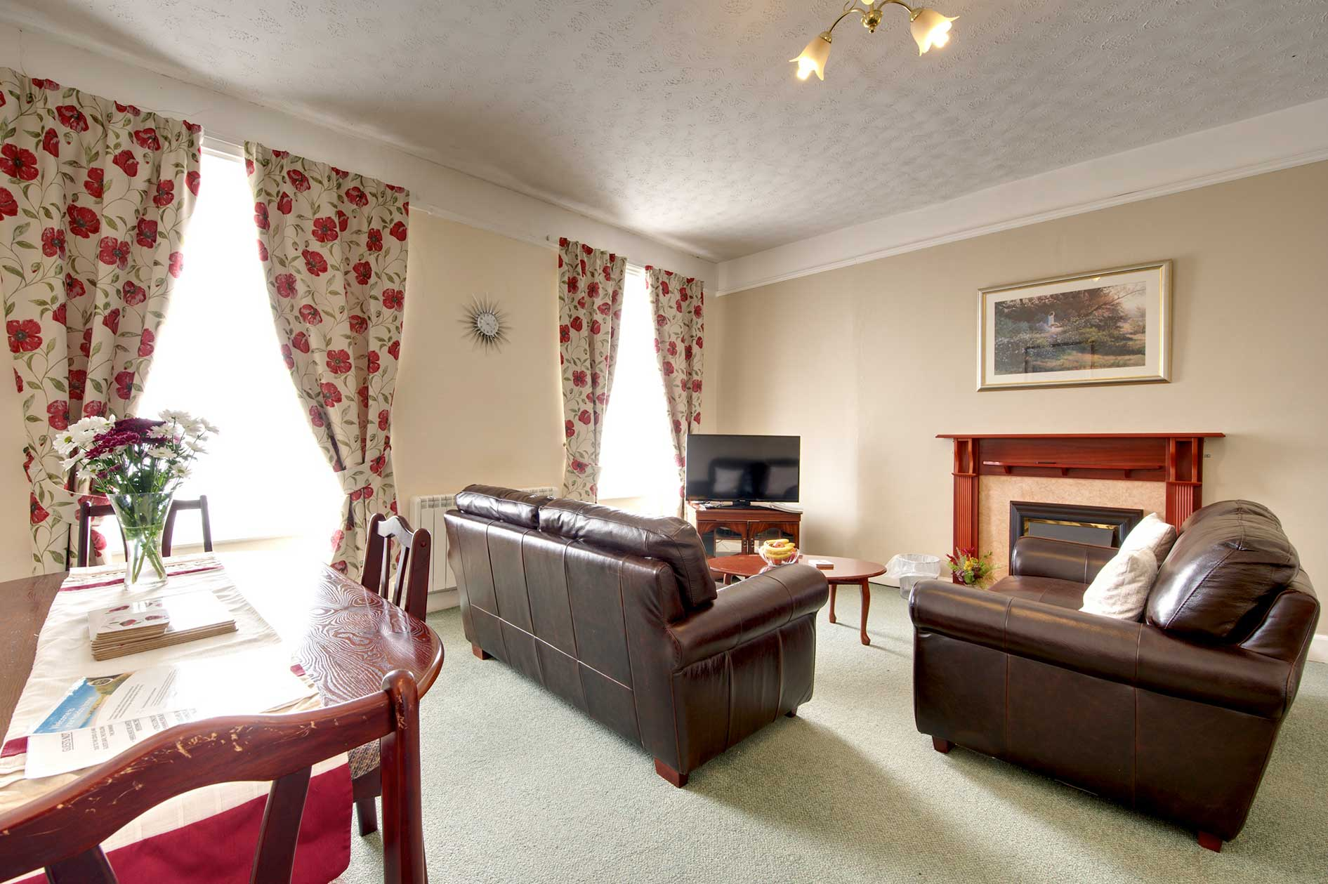 Living Room With Brown Leather Sofas And Red Floral Curtains