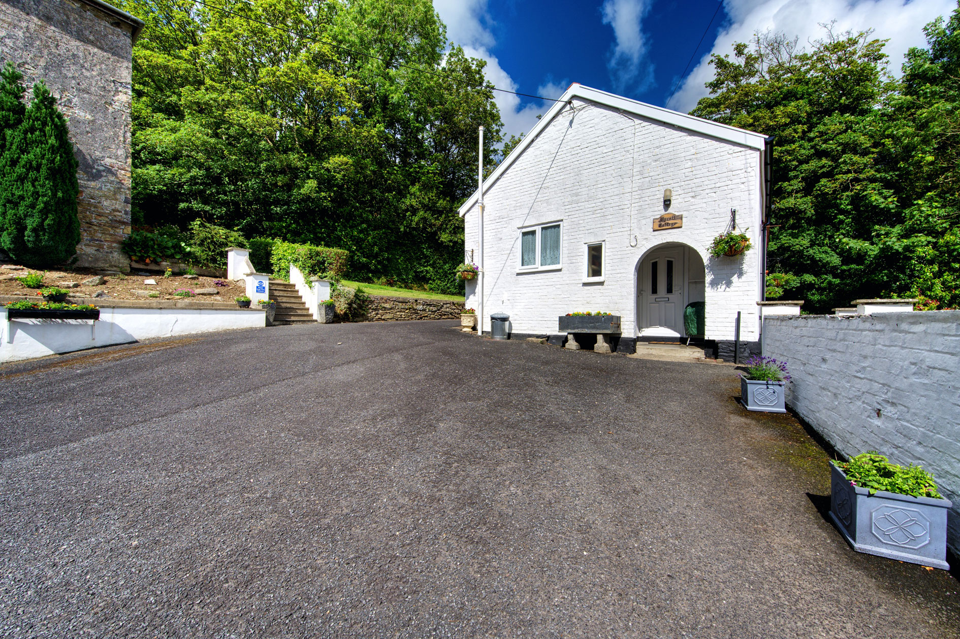 Tarmac Driveways Leading To Small White Building With Trees
