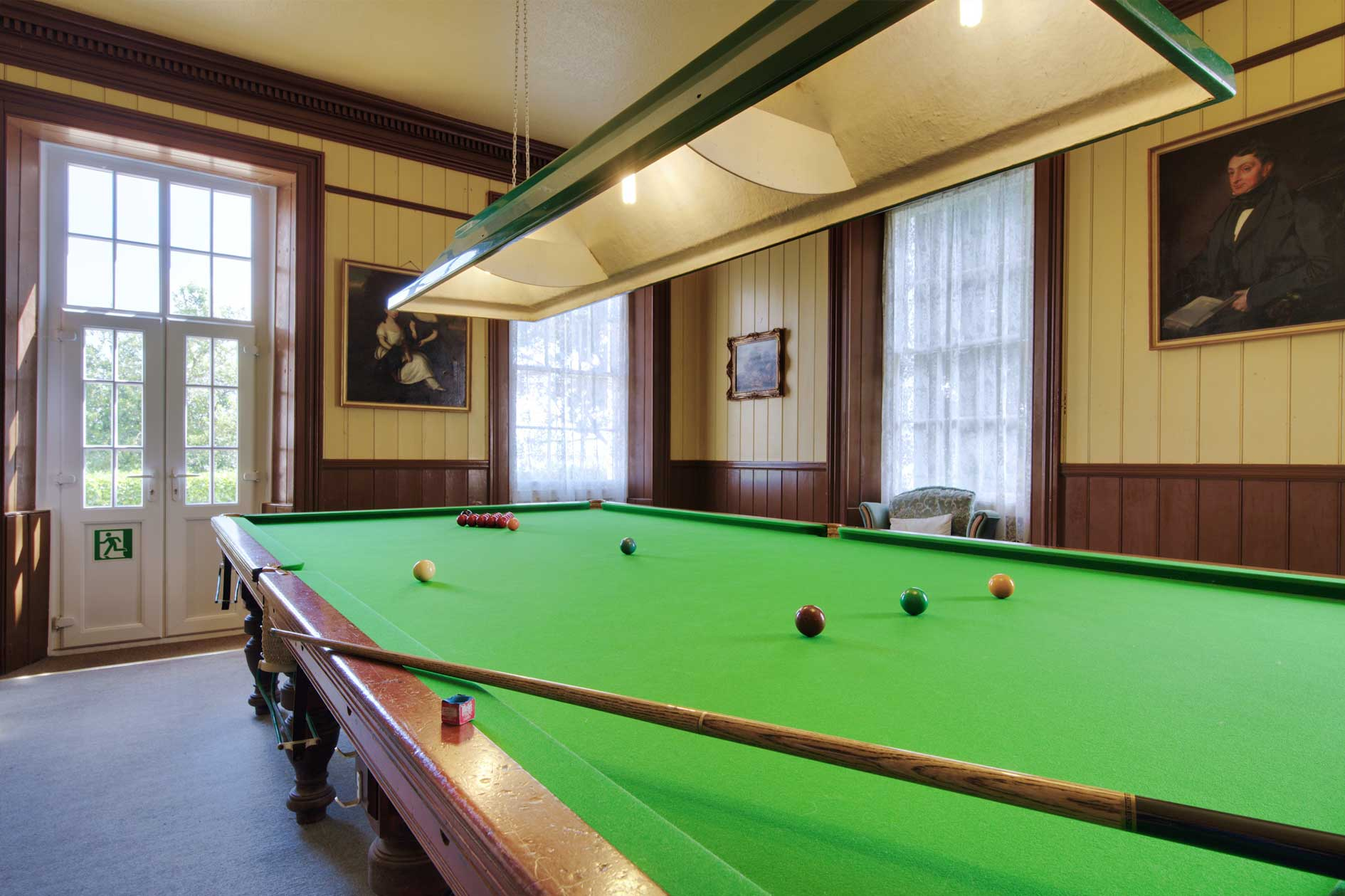 Snooker Table In Room With French Doors And Period Portrait Paintings