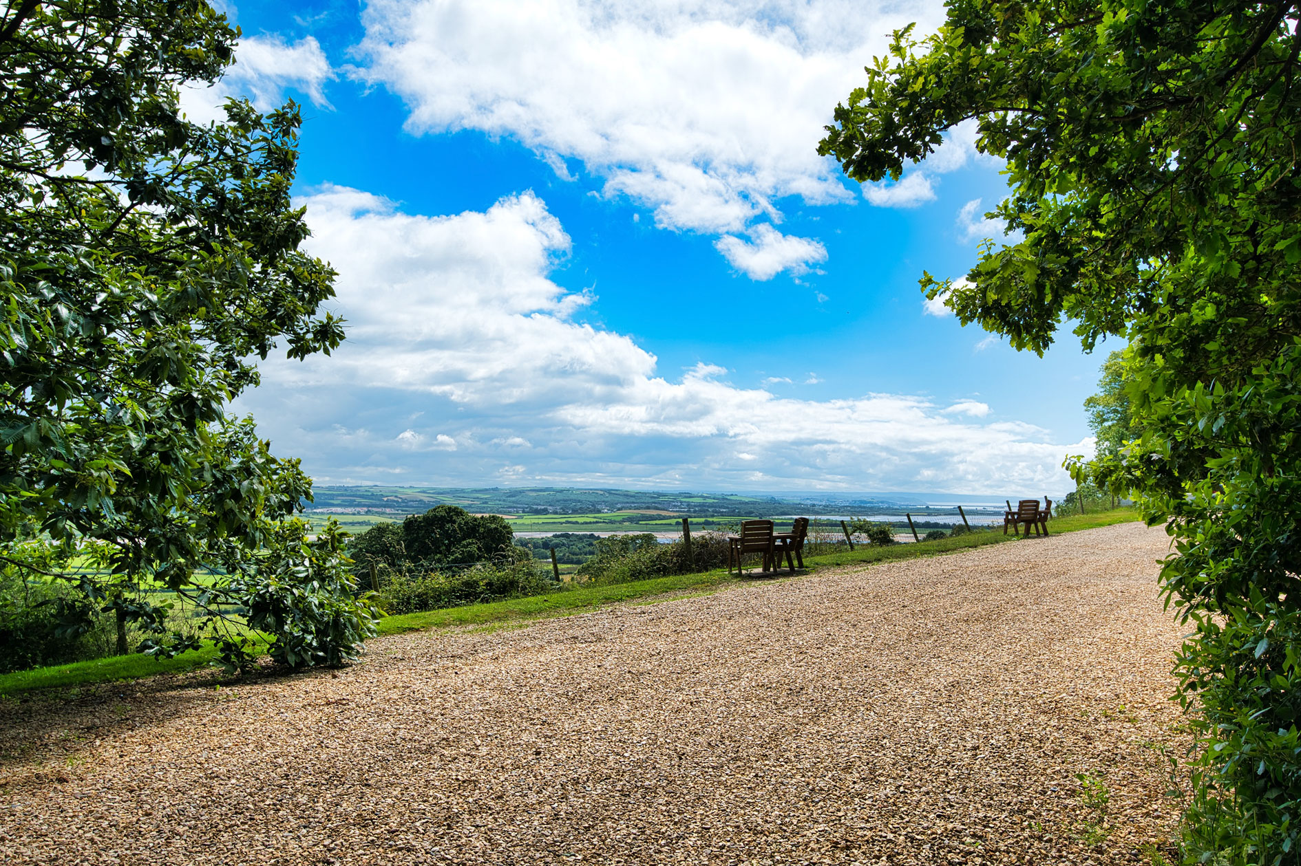 Gravel Driveway With Tress And Distance Countryside Views And Blue Sky